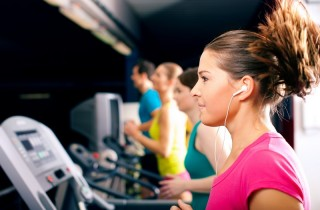 Running on treadmill in gym - group of women and men exercising